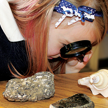 girl looking at rocks and shells with a magnifying glass