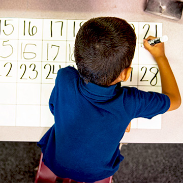 boy at table writing numbers