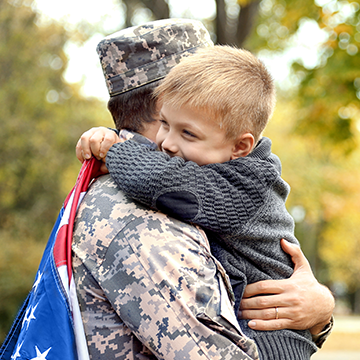 kid hugging dad in uniform